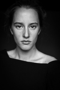 Black and white headshot portrait of a woman looking straight at the camera