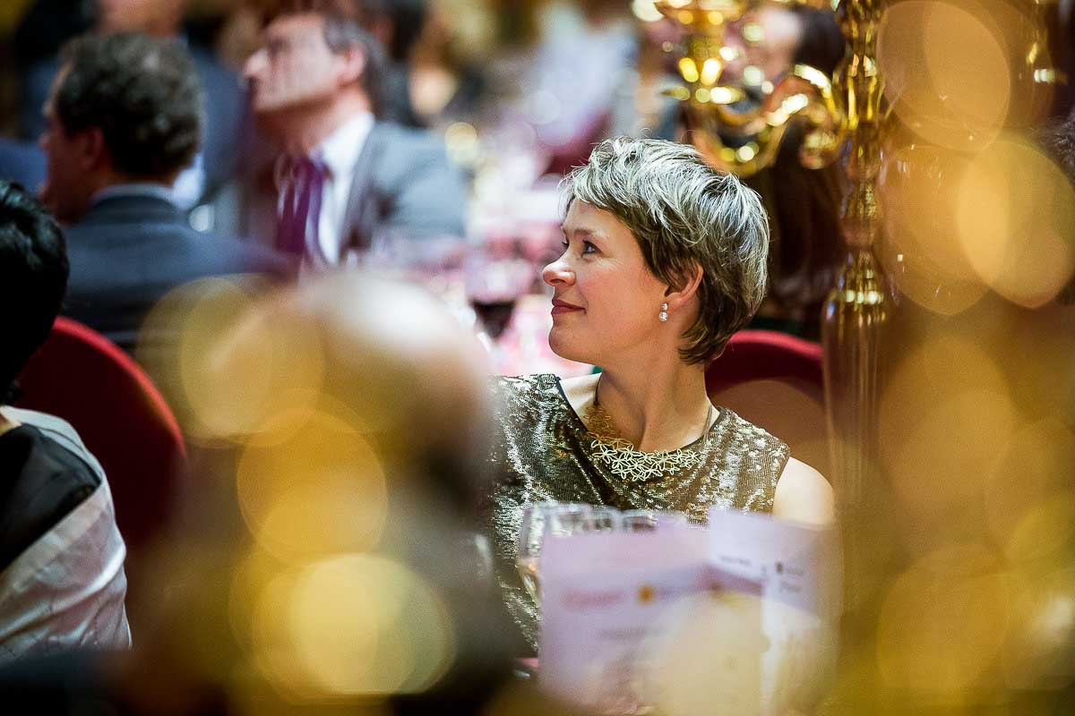 Closeup of a woman in the audience smiling during a Gala dinner event in Brussels