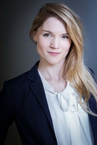 Corporate headshot portrait of a young blond-hair woman wearing a jacket against a dark background