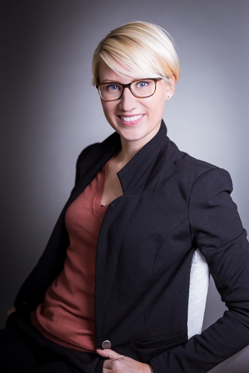 Corporate portrait of a young blond-hair woman with glasses in a suit against a dark background