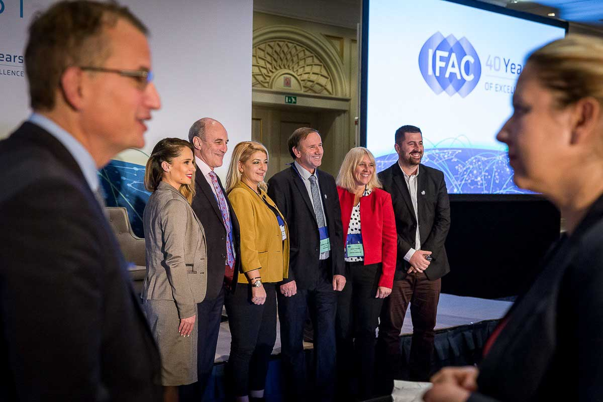 A group of people poses in front of the stage during the 2017 IFAC Conference in Brussels
