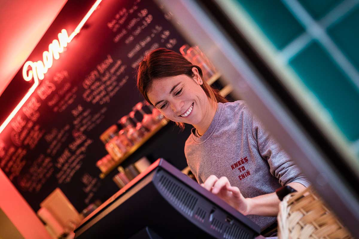 A girl smiles as she taps in the cash register at Knees to Chin restaurant in Sainte-Catherine