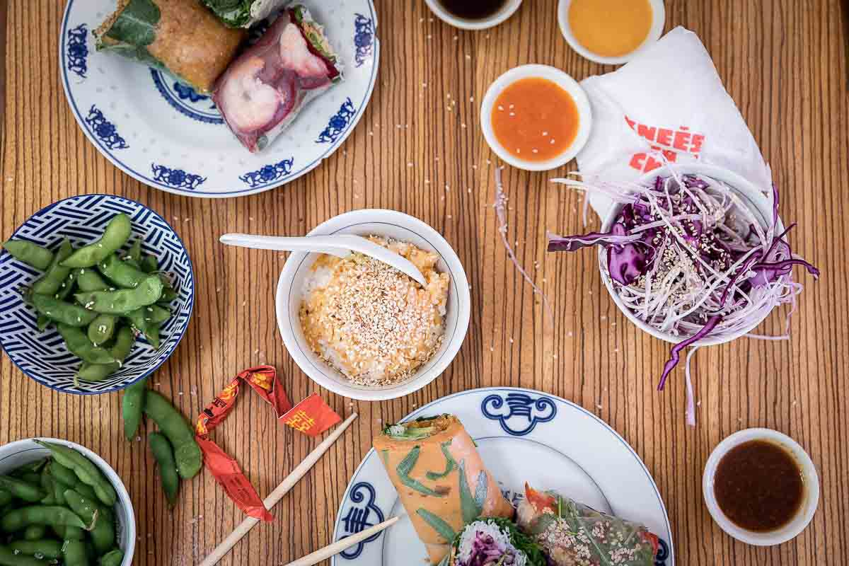 Rice rolls and other foods on a table at Knees to Chin restaurant in Sainte-Catherine, Brussels