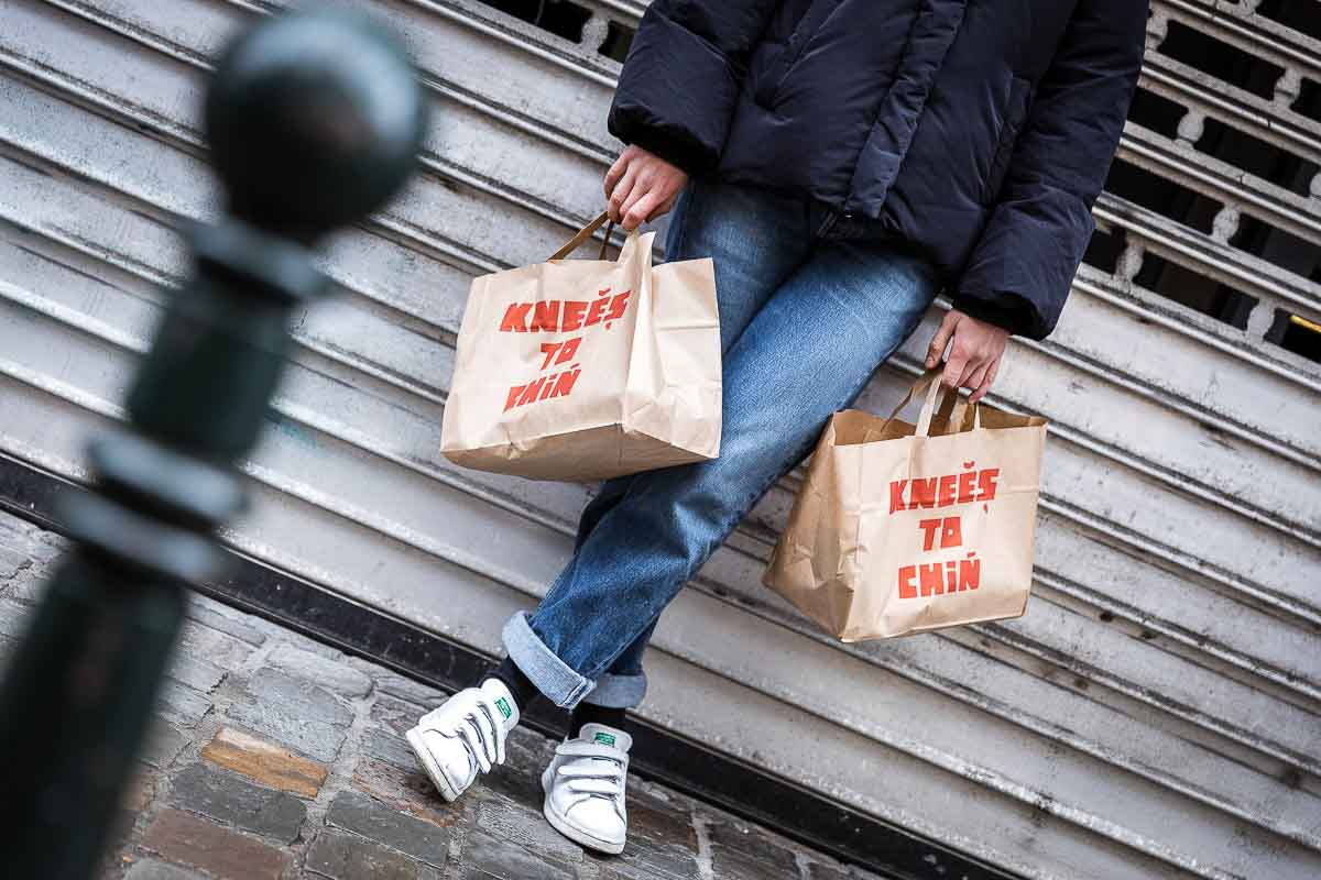 A girl with two bags of food from Knees to Chin restaurant in the street