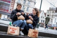 Two girls eating food from Knees to Chin in the street at Place Sainte-Catherine, Brussels