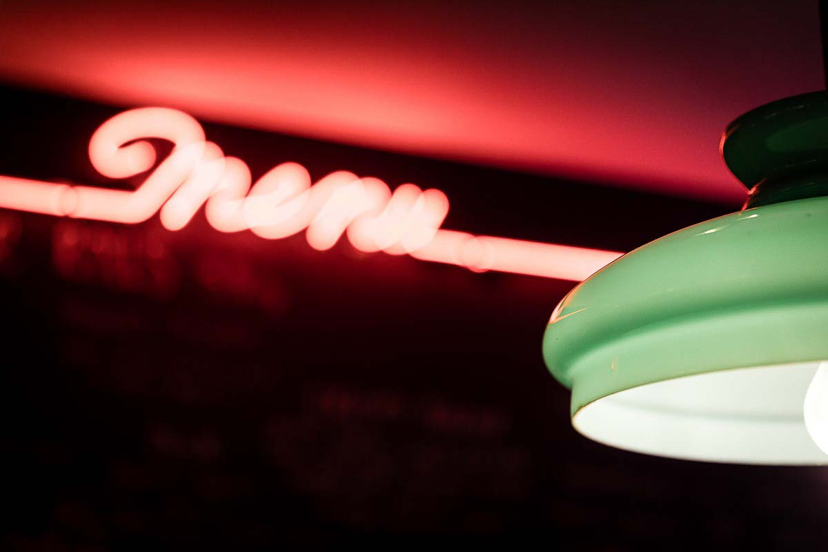 Green lamp and neon light detail inside Knees to Chin restaurant in Sainte-Catherine, Brussels