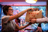 A waitress from Knees to Chin hands a take-away bag to a client