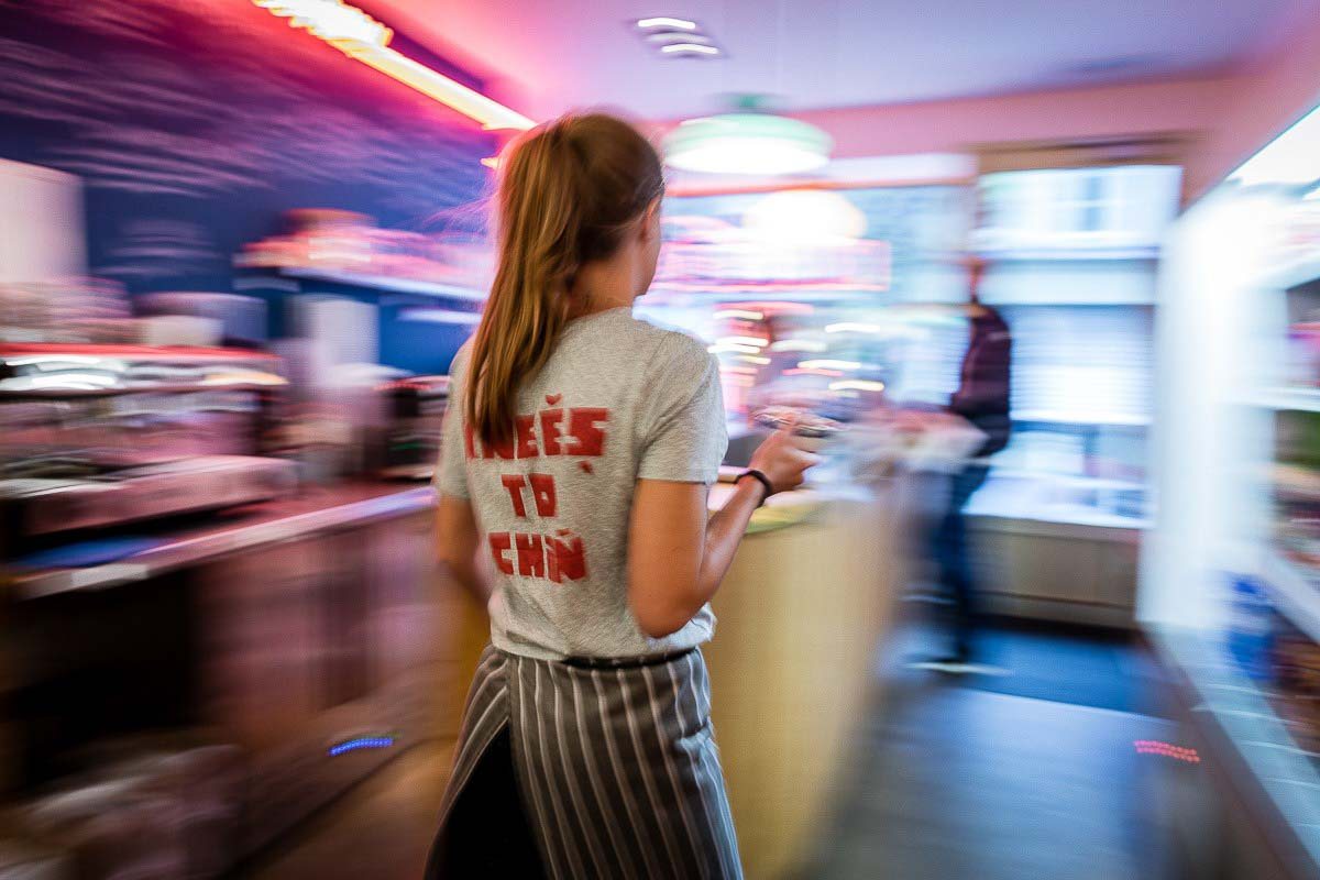 A waitress moving taking food to a client at Knees to Chin restaurant in Sainte-Catherine, Brussels