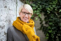 Portrait of a young blond-hair woman smiling wearing glasses, a grey jacket and a yellow scarf