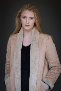Headshot portrait of a blond woman wearing a beige coat against a dark background