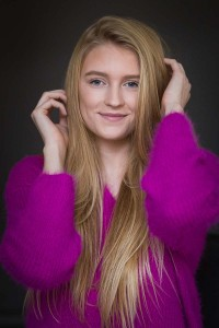Headshot portrait of a blond woman wearing a fuchsia sweater against a dark background