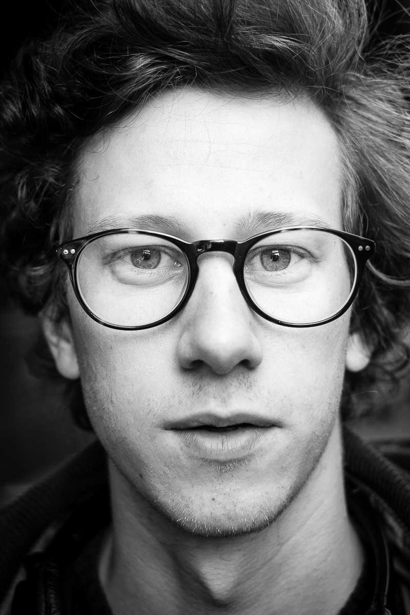 Black and white closeup portrait of a man with glasses from Belgium taken in Brussels