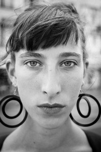 Black and white closeup portrait of a woman with big earings from France taken in Brussels