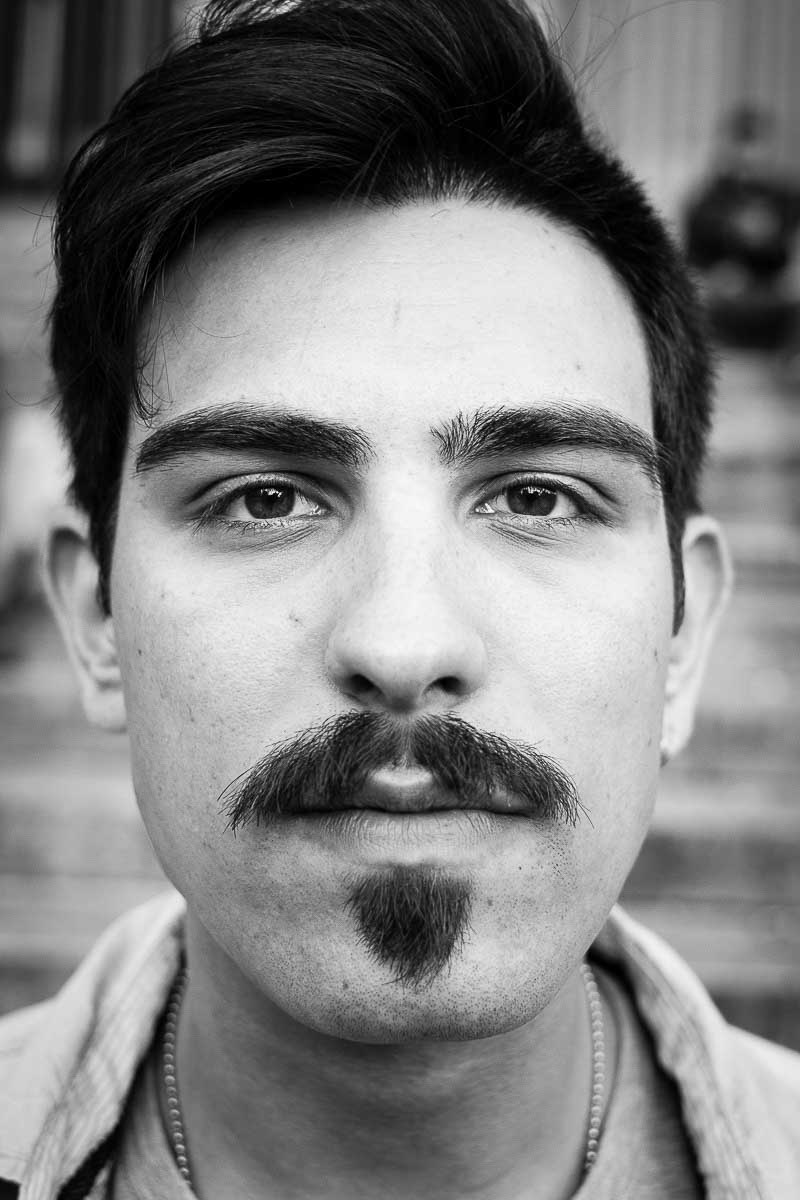 Black and white closeup portrait of a man with a moustache from Italy taken in Brussels