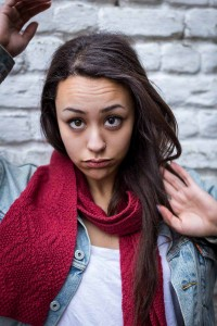 Portrait of a dark-haired woman wearing a jean jacket and a red scarf against a white brick wall