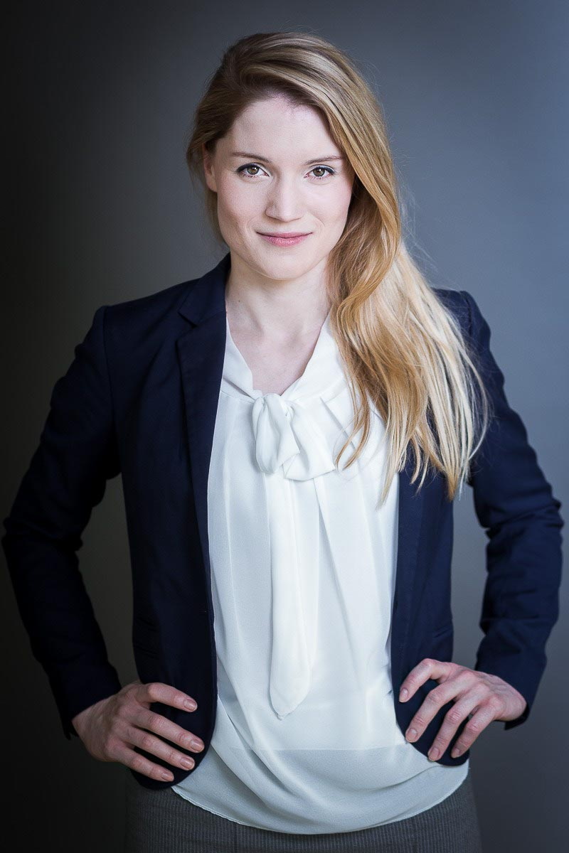 Corporate portrait of a young blond-hair woman wearing a jacket against a dark background