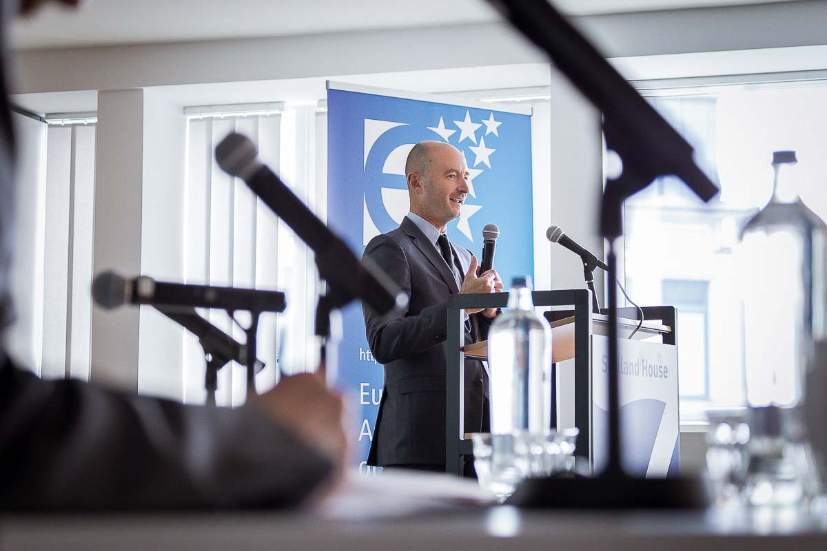 A speaker seen through several microphones during a conference for EURADA in Brussels