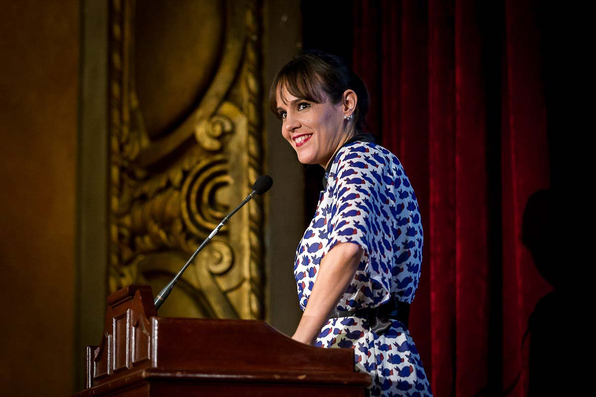 A woman speaker smiles while addressing the audience during a Gala dinner event in Brussels