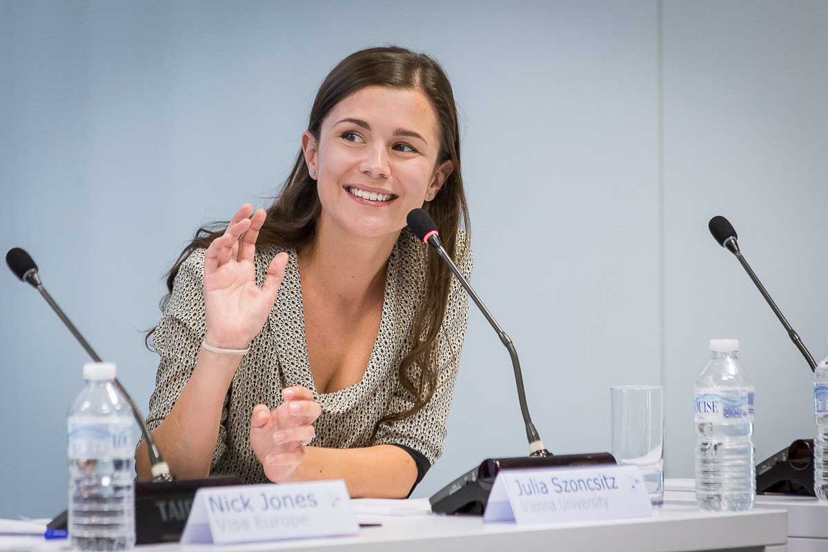 A woman speaker smiles and salutes in a conference for JA Europe in Brussels