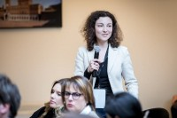 Photograph of an attendee asking a question using the microphone in an event for EURADA in Brussels