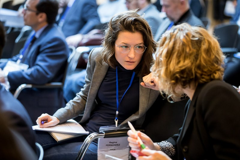 A woman engaging with a participant in the audience during an event for EURADA in Brussels
