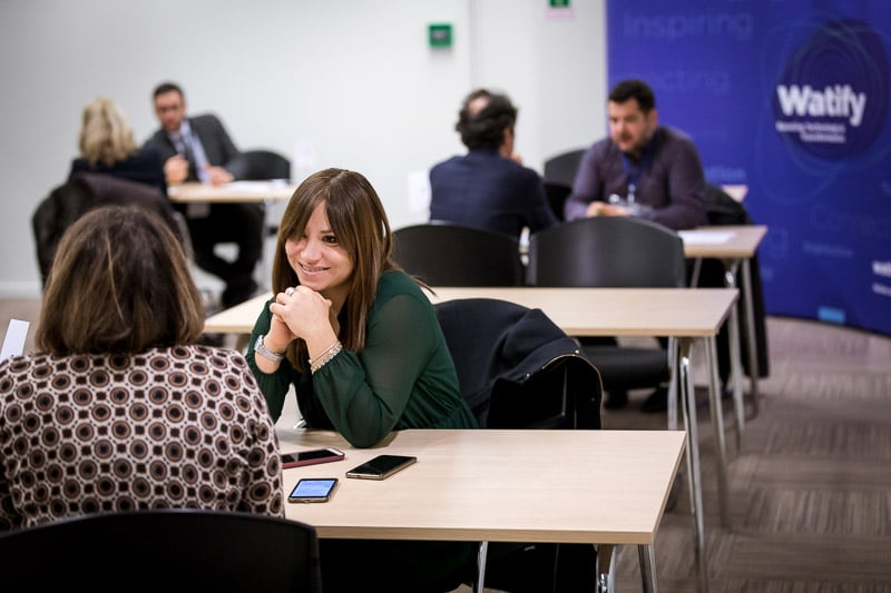 Photography assignment for EURADA - Photo of an attendee speaking with another person while she's smiling - Photography by Dani Oshi in Brussels