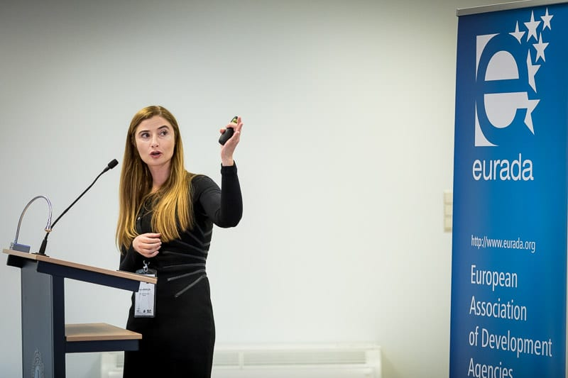 A speaker moving her left hand up while explaining her slides to the audience