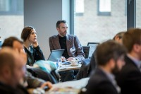 An attendee listens to the speaker during a workshop event for EURADA in Brussels