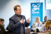 An attendee engages with a speaker during a workshop event for EURADA in Brussels