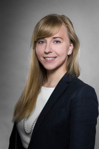 Corporate headshot portrait of a blond woman wearing a dark jacket against a gray background