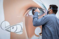 A graffiti artist working on a piece with sprays at the Groenplaats, Antwerp
