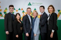 A group of people pose in front of a banner for a JA Europe event in Brussels