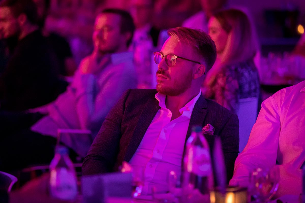 A guest with a concentrated gaze listens to a speaker during a gala dinner event in Brussels