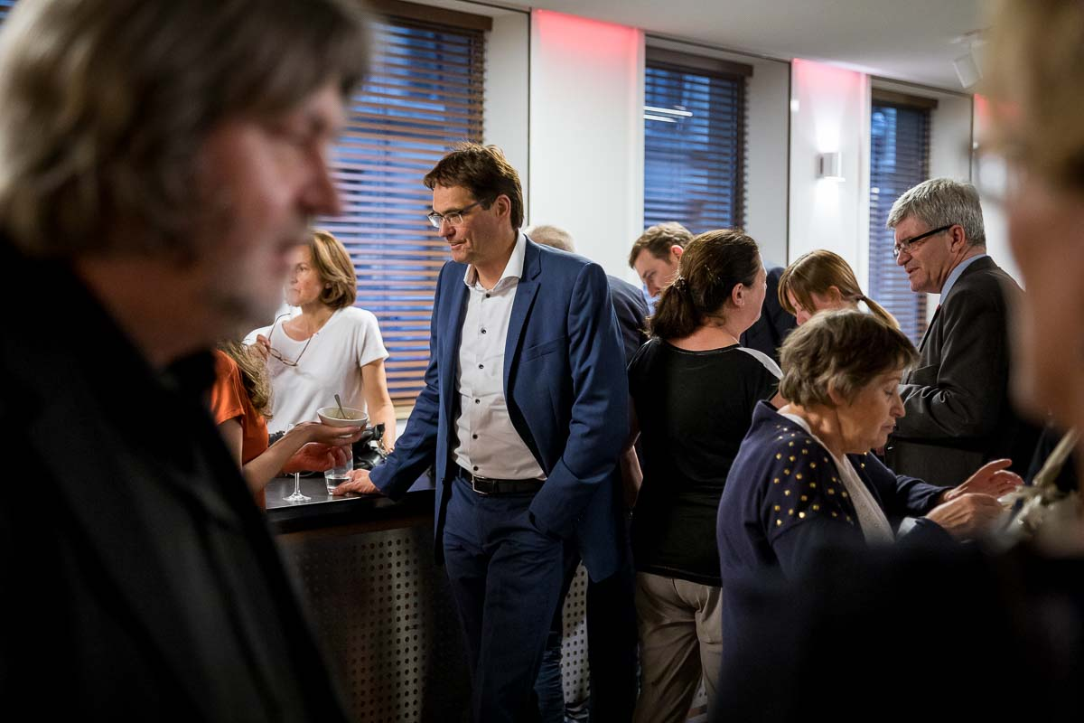 A guest talks to other guests during an walking dinner event in Brussels