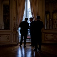Guests looking by the window during an event at the Palais d'Egmont in Brussels