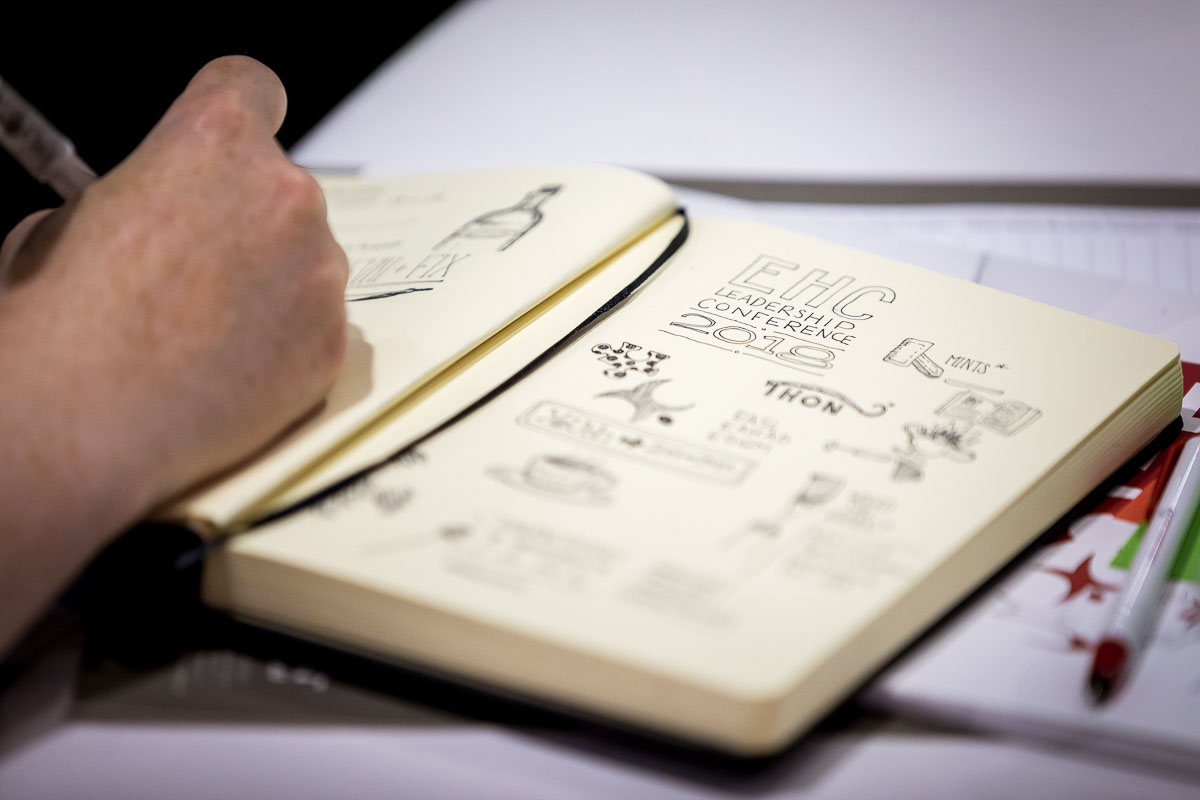 Closeup of a hand writing on a notebook during the EHC 2018 in Brussels