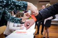 Closeup of a pair of hands putting a wristband to an attendee during a conference in Brussels