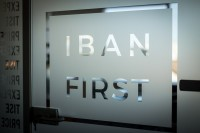 Detail of a glass door with the words IBAN FIRST on it