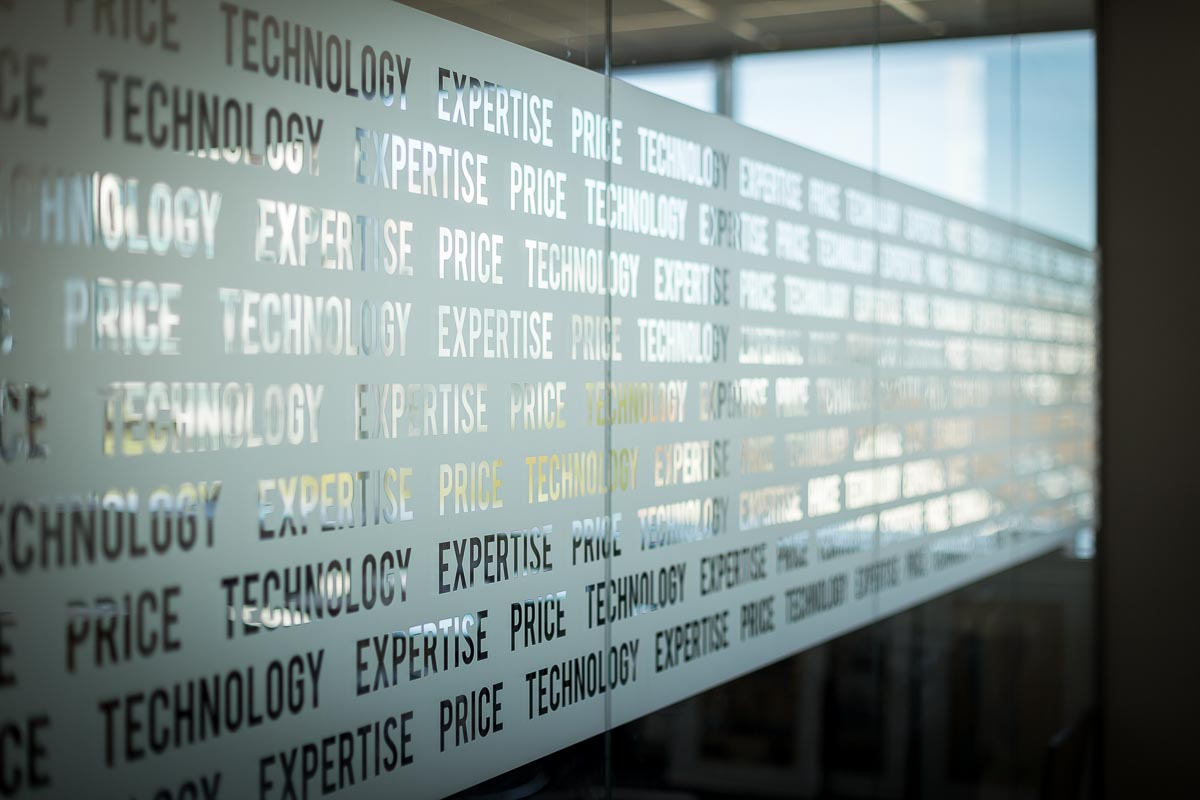Detail of a glass window with the words Technology, Price and Expertise on it for IBAN FIRST