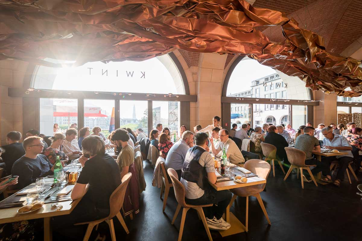 Interior of KWINT restaurant showing customers during a sunset in Mont des Arts, Brussels