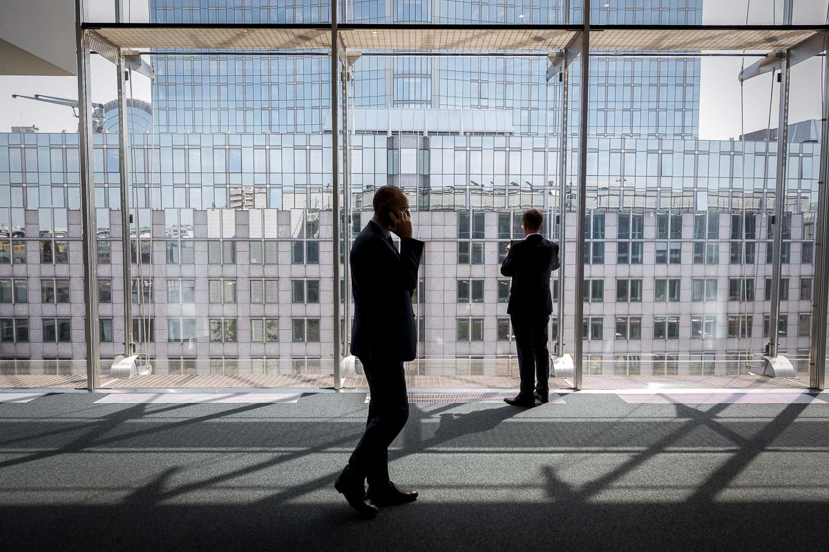 A man walks in front of a window inside the European Parliament in Brussels