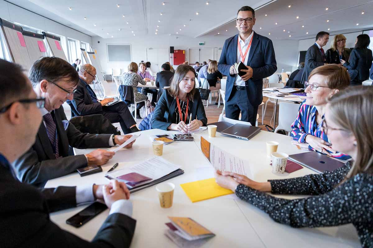 A round table of people doing a network activity during a conference in Brussels