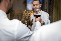 A waiter hands a wine glass to a guess during a dinner event at Hispania, Brussels