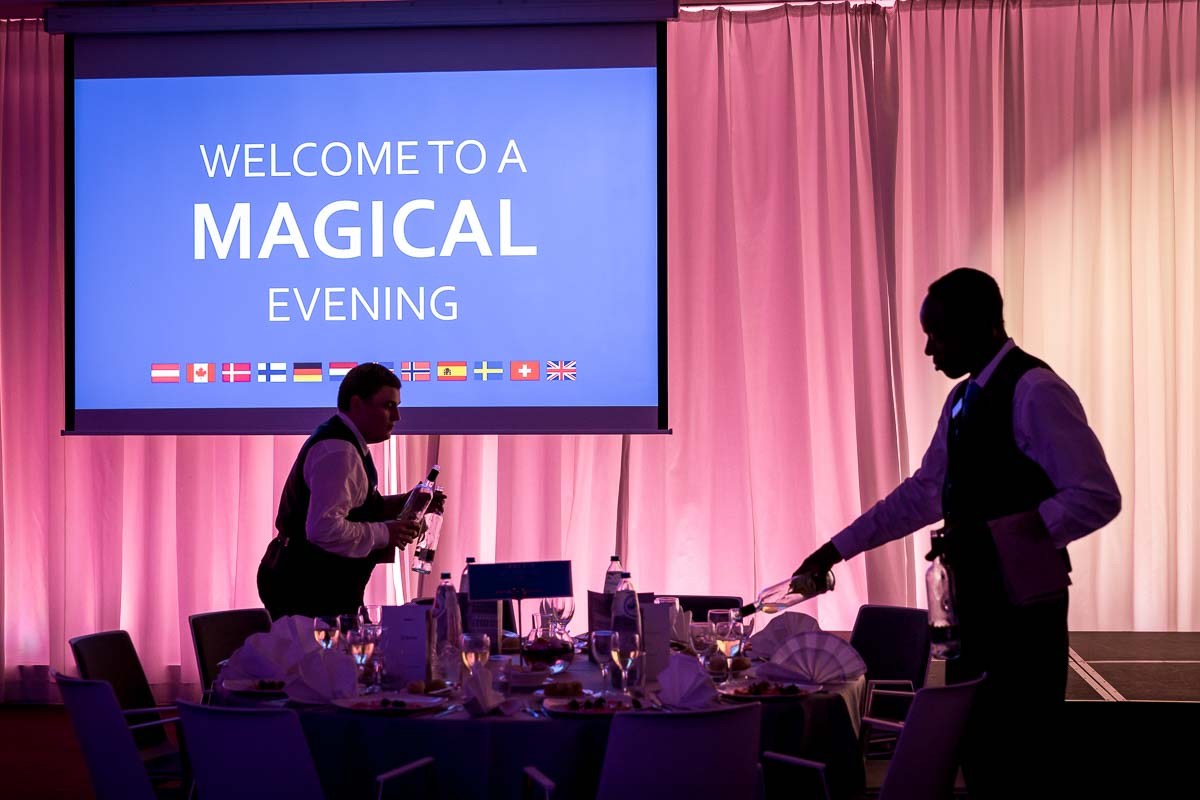 A screen announces 'Welcome to a Magical Evening' during an event in Brussels