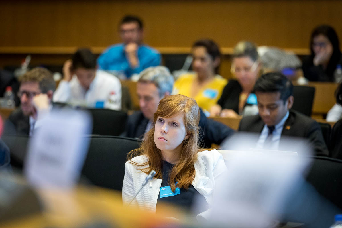 A woman from the audience listens carefully during the EPP Group conference in Brussels