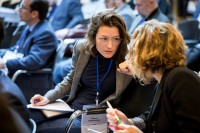 Closeup of a woman from the audience talking to another guest during a conference in Brussels