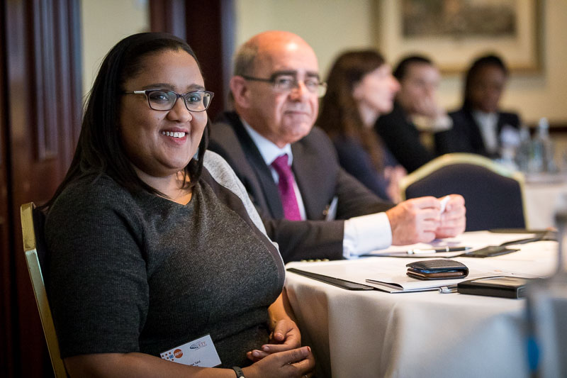 Conference Photography: Closeup of a guest smiling as she listens during a meeting for the EPF