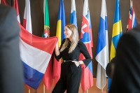 A girl poses for a picture holding the flag from The Nederlands during the Why Europe Matters 2018 for JA Europe