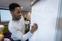 A student writing in a white paper board during the Why Europe Matters 2018 for JA Europe