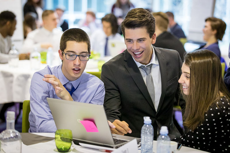 Three students smiling and discussing during the Why Europe Matters 2018 for JA Europe